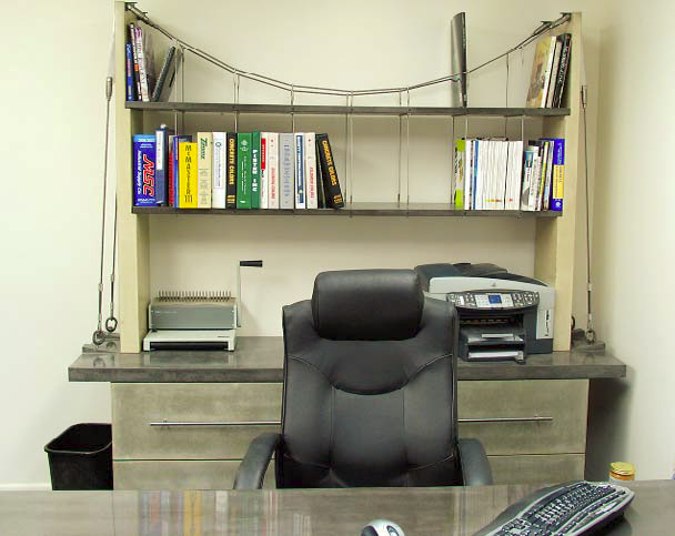 This office is fully equipped with concrete office furniture such as a bookshelf and a desk.