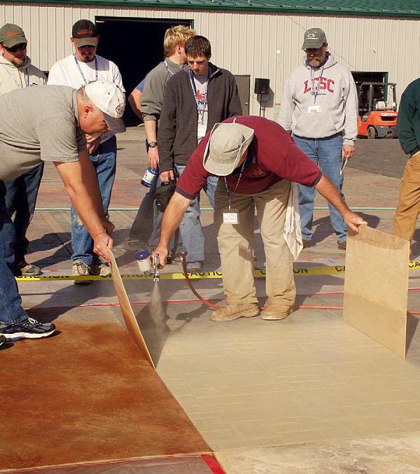 Smith Paints' Hugh Monteith demonstrates Smith's Color Floor water-based stains at this year's Northwest Decorative Concrete Events in Milton-Freewater, Ore. Monteith is applying CF-250 Desert Sand while Mike McDonald, Smith's Northwest regional manager, shields a slab stained with CF-630 Amber.