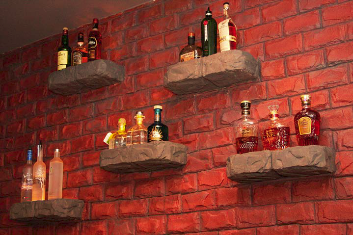A stamped brick wall has custom concrete shelves added in for an entire cohesive look.