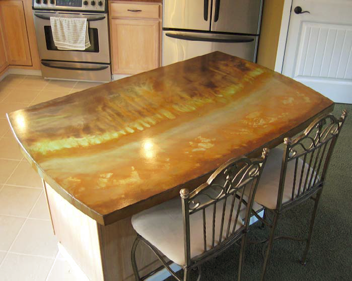 Concrete countertop with browns and oranges give this kitchen island a natural stone look.