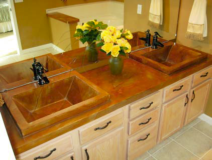 Two concretes sinks in the bathroom vanity that takes on orange and brown hues.