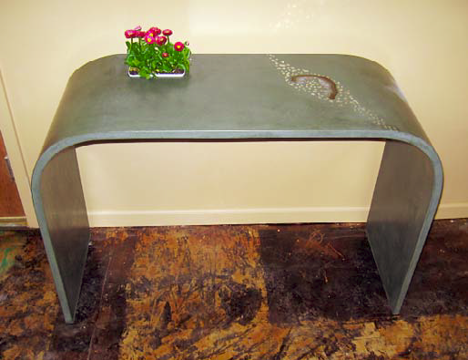Thin concrete is cast in one continual piece to create this hall table making the table look bent.
