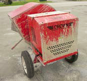 A concrete mixer covered in concrete in need of a cleaning.