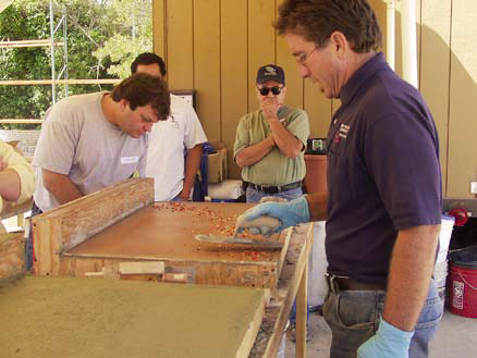 Tom Ralston of Tom Ralston Concrete demonstrates glass embedment to his crew members.