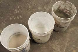 Three 5-gallon buckets containing three ingredients used in creating GFRC mix for concrete countertops.