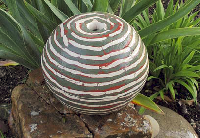 Concrete ball striped with gray, white and red colors in front of a fern.