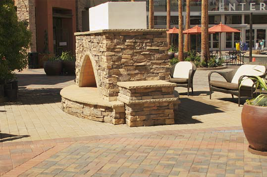 Concrete fireplace creates a nice resting place on this outdoor patio.