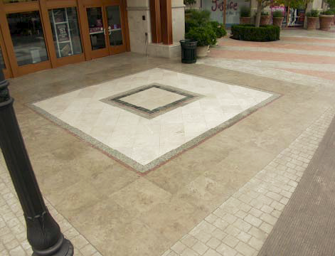 Concrete courtyard in browns and whites with a square pattern.