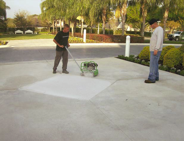 Using a cutter to cut the concrete into the proper shapes and design.