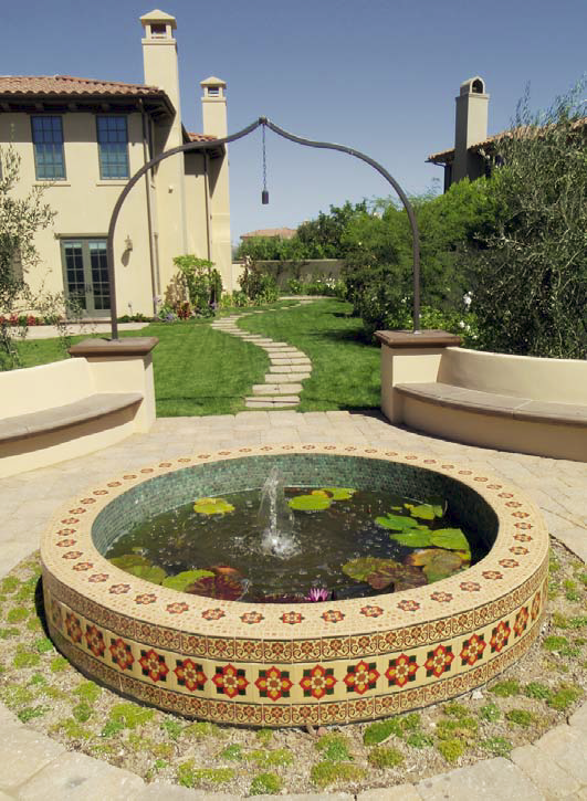 Concrete fountain and koi pond blend in naturally with his pool deck design.