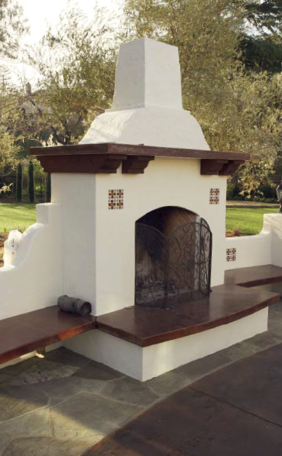 A look at an adobe style custom concrete fireplace on a pool deck.