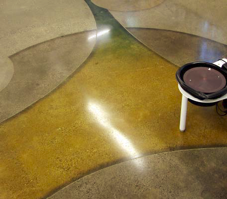 Gradient colors from yellow to green are dyed into this polished concrete floor.