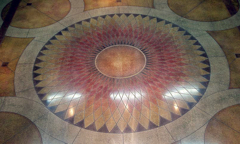 Polished concrete with a geometric pattern engraved, colored and polished to look like a large flower.