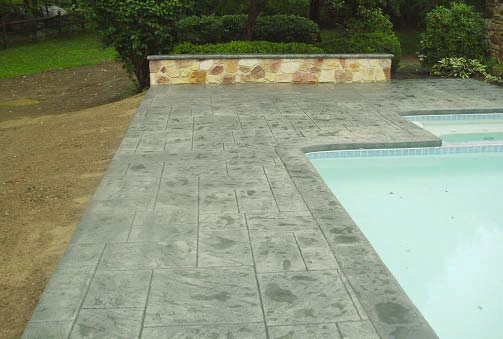 Concrete pool deck in gray with a stamped patter on top.
