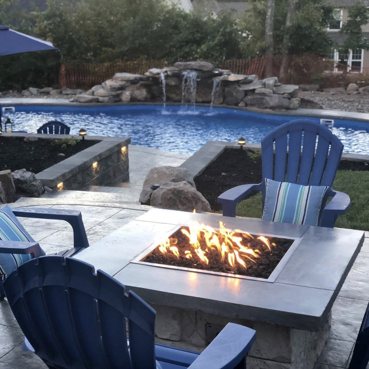 Outdoor patio space with a firepit in the forefront and the pool in the back.