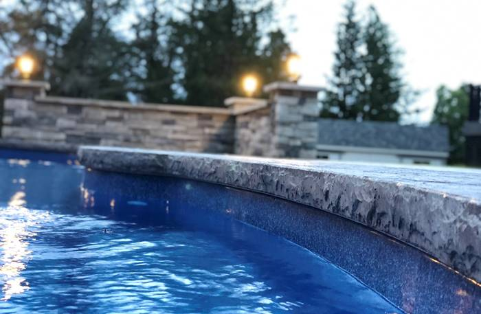 Chiseled stone around a pool deck is a popular edge from