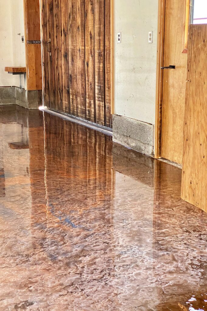 This metallic epoxy floor has a charred wood look that matches the barnwood on the exterior.