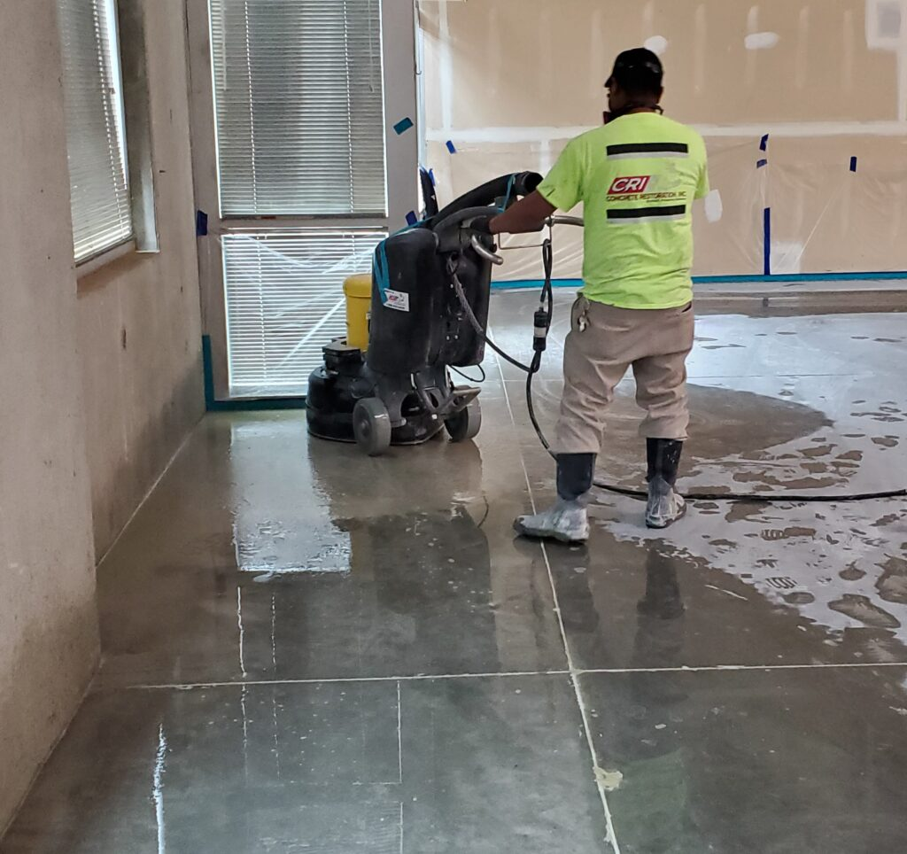 A polishing contractor using a grinder to polish a concrete floor.