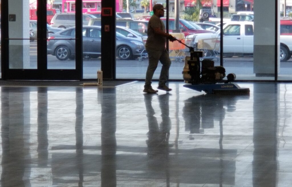 A contractor on a shiny polished floor with a burnisher
