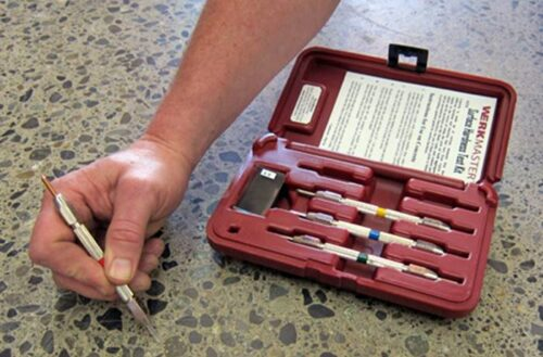A hand next to a mohs testing kit
