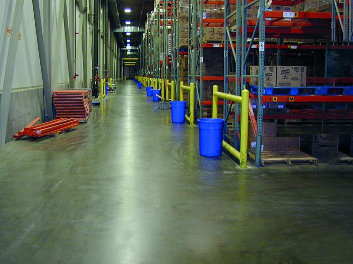 A warehouse with a concrete floor and shelving lining walls.