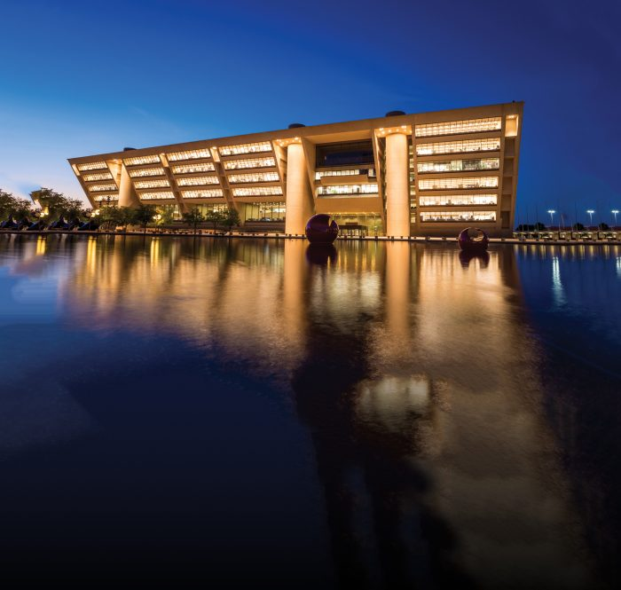 A large building with bright windows and columns made of concrete reflecting off of a nearby body of water.
