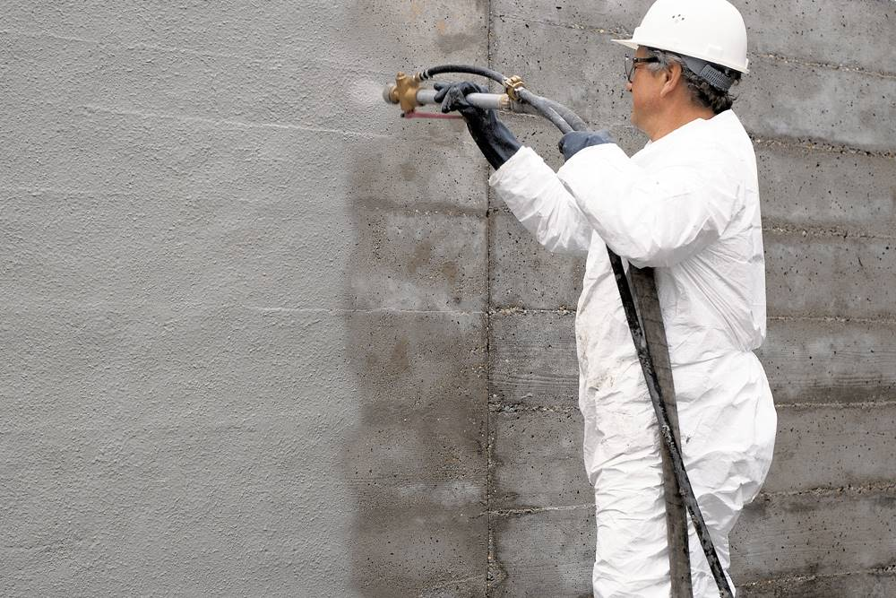 a person in a full protective suit spraying concrete coatings on a vertical concrete wall