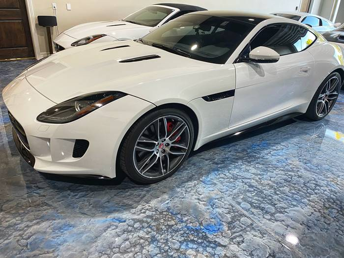A Jaguar F-Type parked on a metallic epoxy garage floor in blues and grays