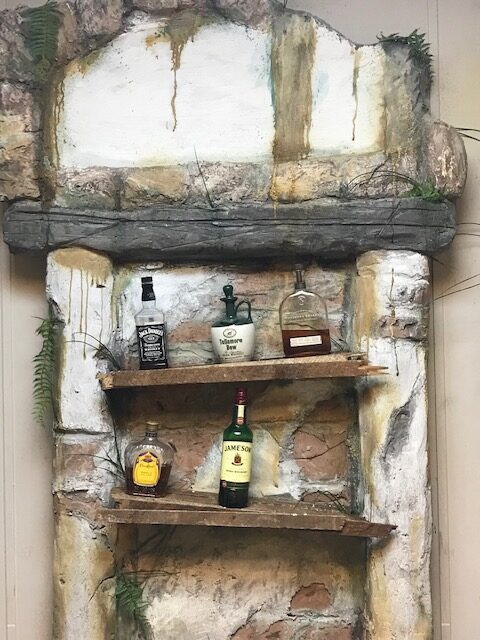 A custom crypt-like liquor shelf was created in the office for the finishing touch.