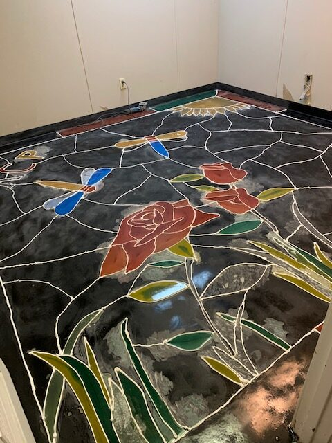 A look at a floor with flowers and dragonflies that will be a home office that looks like stained-glass.
