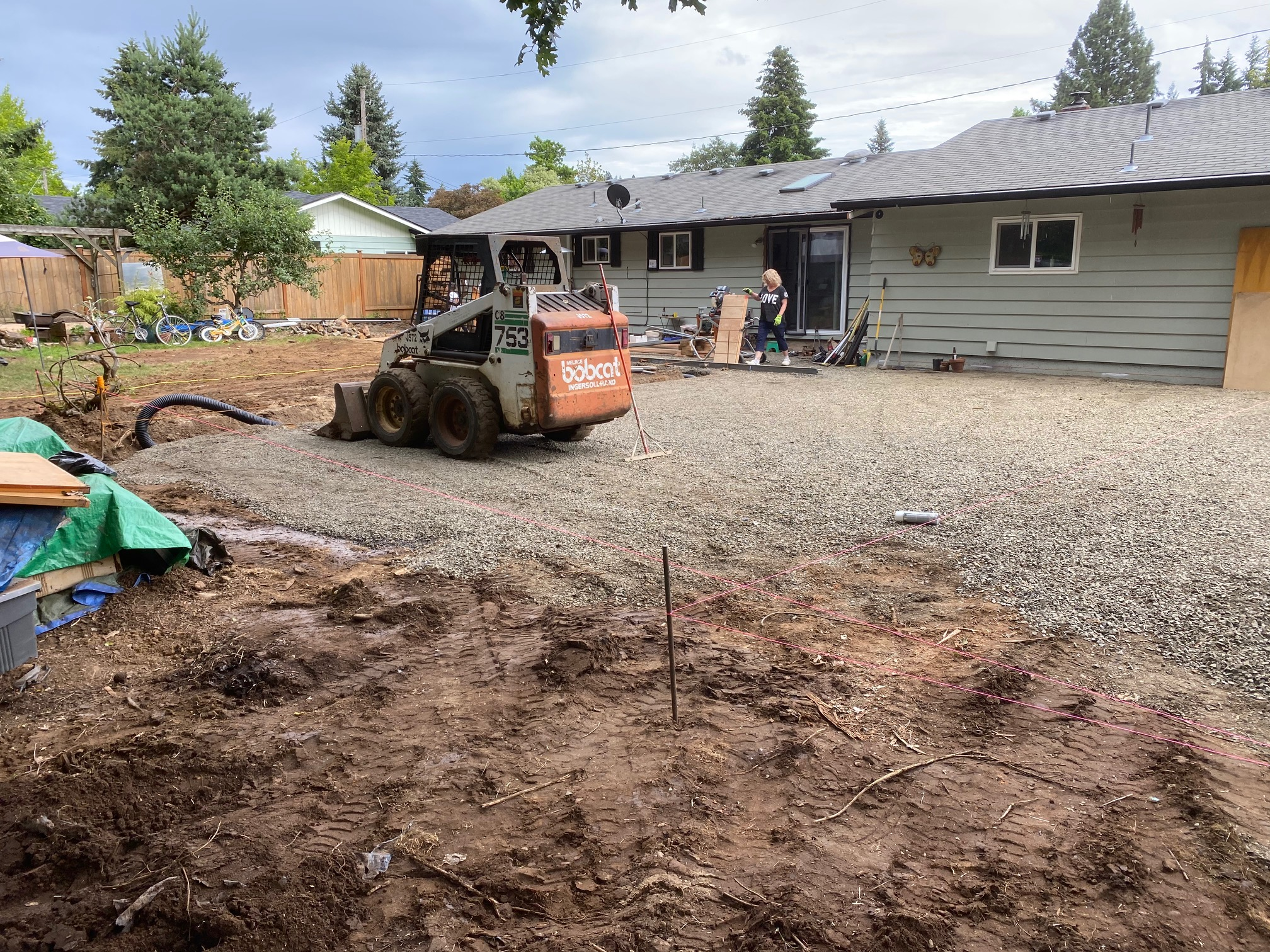putting in the hard work using a Bobcat to flatten the gravel before a concrete pour