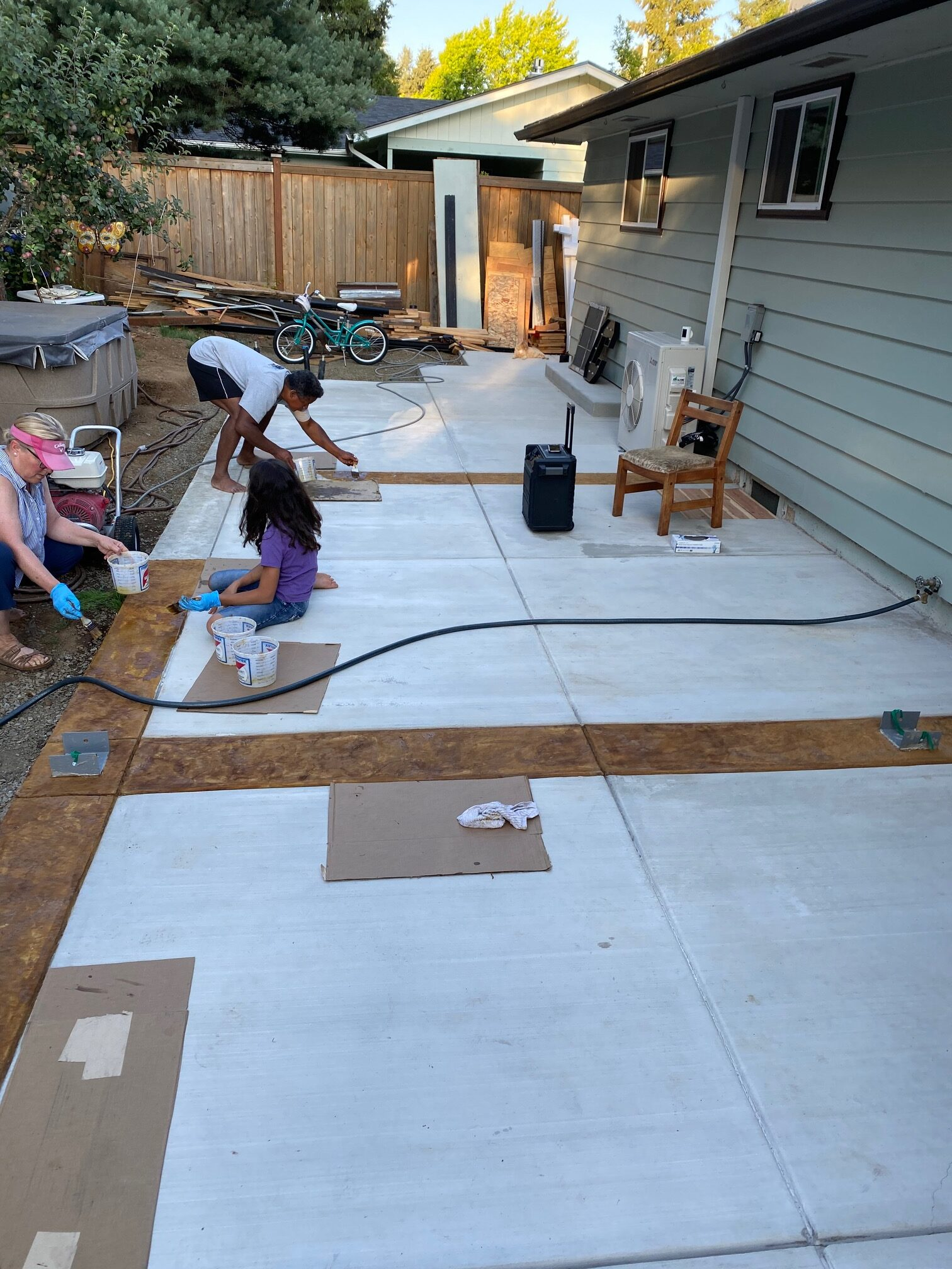 the homeowners staining and texturing the borders of the concrete patio