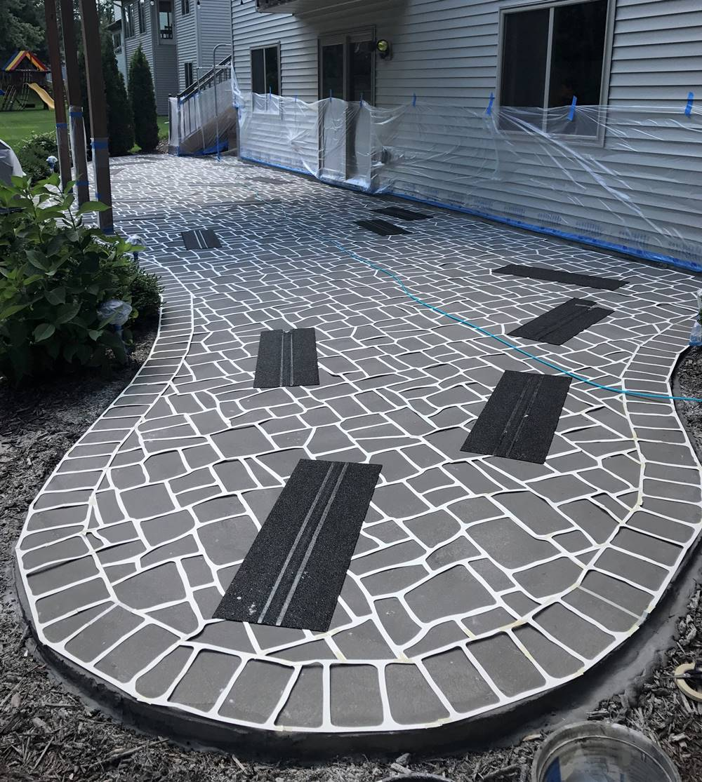 The placement of stencils on a concrete patio