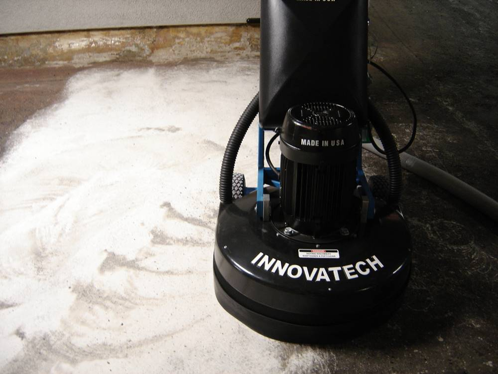 a grinder by Innovatech removing adhesive from concrete