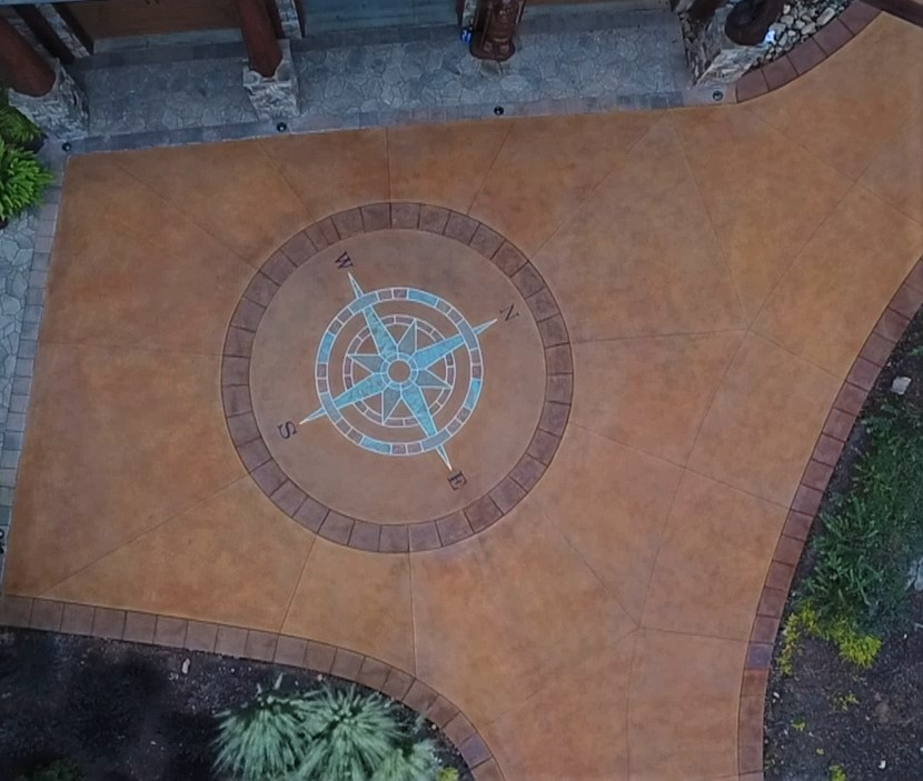 A large compass placed in the middle of a stained concrete driveway is the latest project for Ben Bass who has turned to the decorative side of concrete