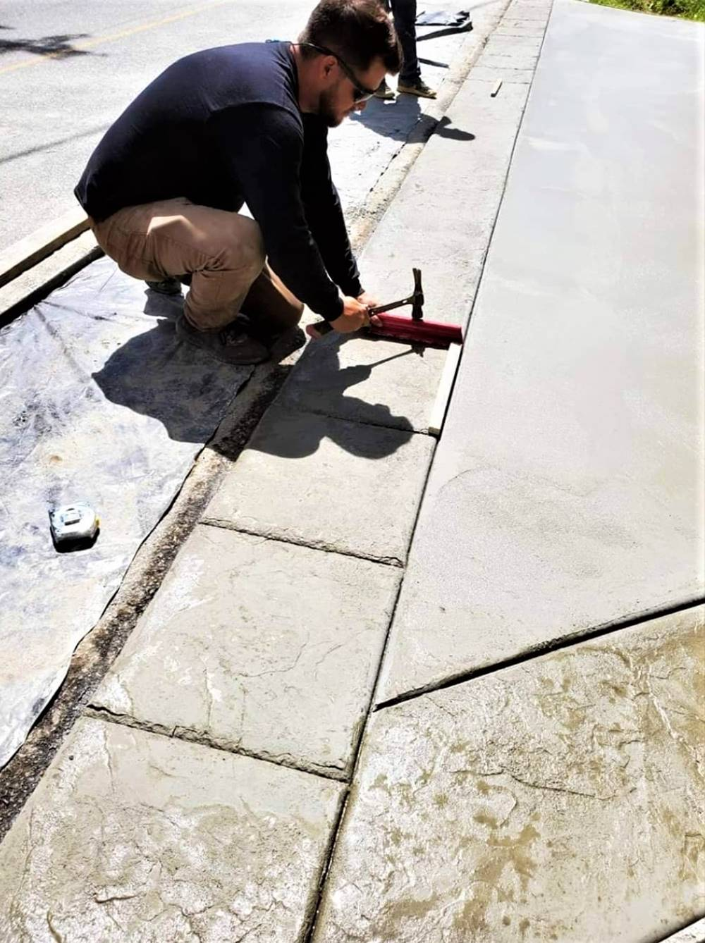 chiseling out the grout lines of a concrete driveway.