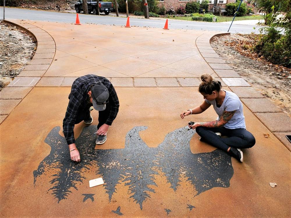 A crew putting the finishing touches on a stencil in the driveway