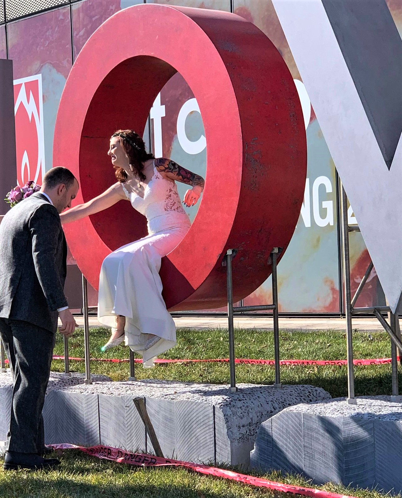 a bride posing in the O of the LOVE concrete sculpture