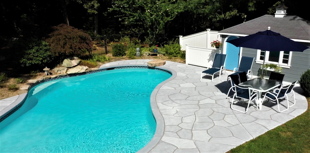 A pool deck with a bright blue pool. The pool deck has been transformed with RenuKrete systems.