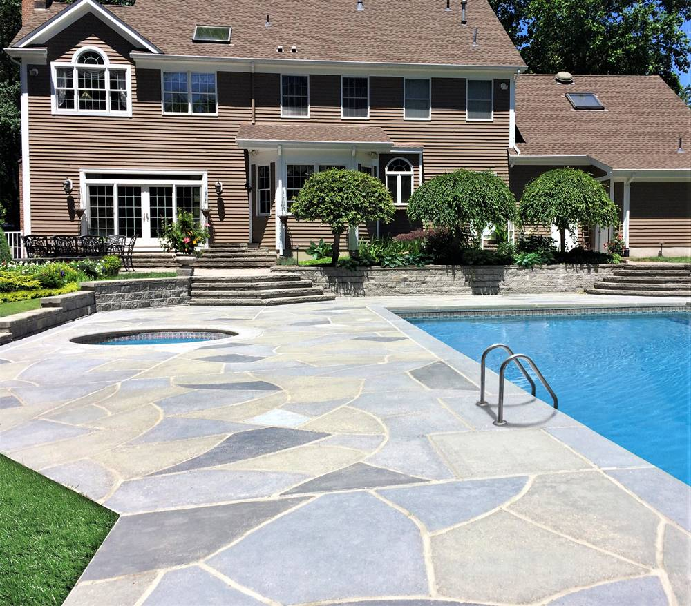 A large home overlooking a pool deck that has been transformed with RenuKrete product.