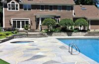 A pool deck finished with Renu-Krete products in front of a brown home
