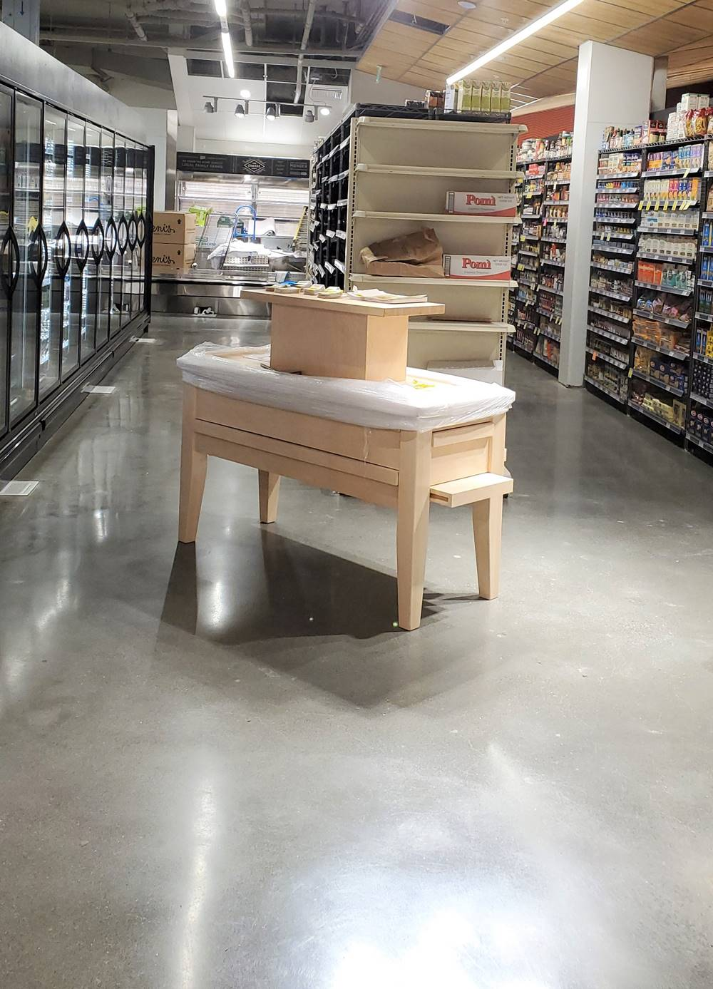 A floor in a grocery store with finished concrete in natural gray