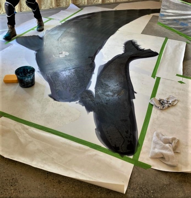 Using the custom-made stencils to create whales using black dye