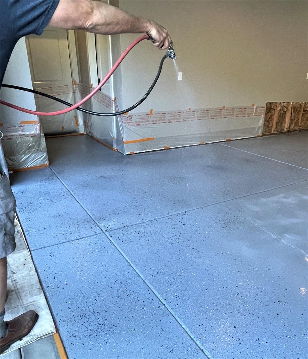 sprating the liquid chip system onto a garage floor using an HVLP sprayer