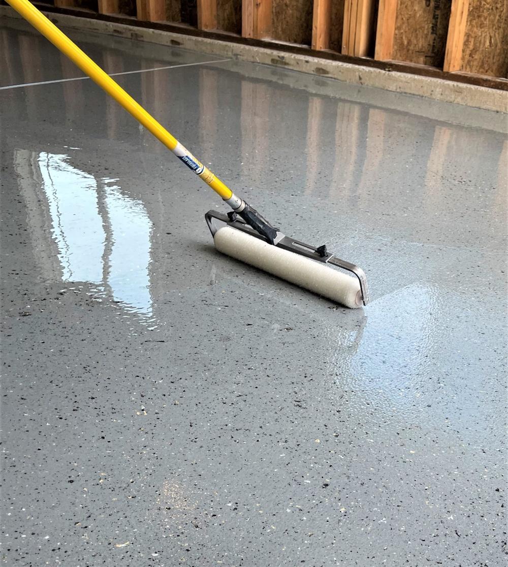 Rolling the top coat onto a garage floor