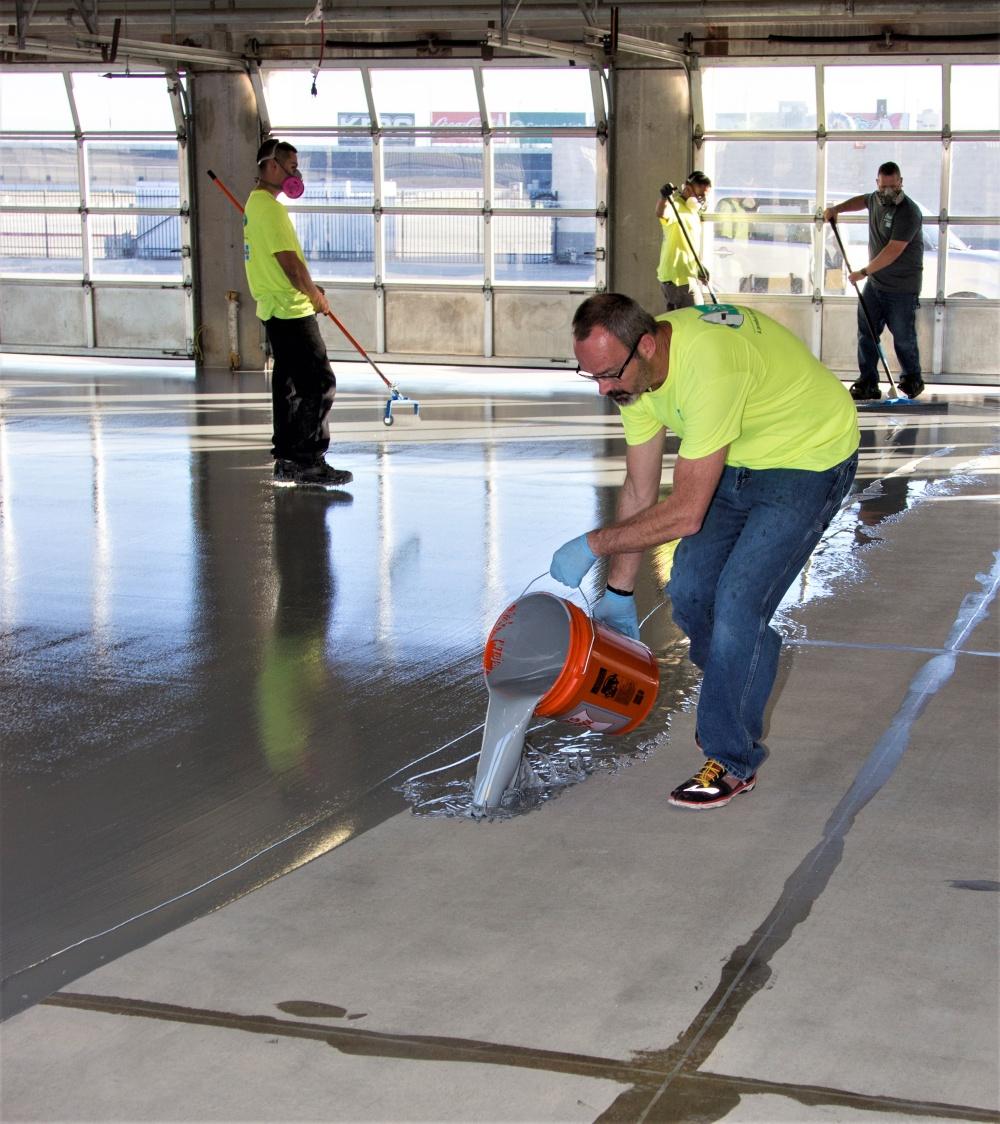 pouring a pigmented moisture mitigator by Laticrete onto the concrete floor