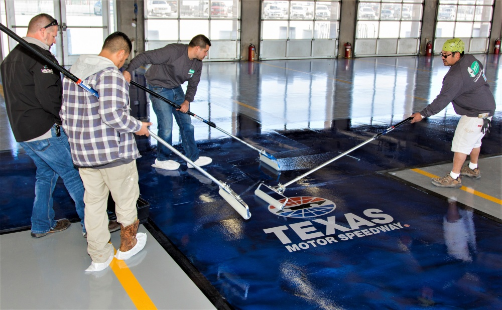 applying a custom stencil logo to the concrete floors at the Texas Motor Speedway