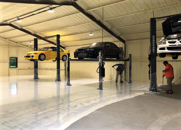 Applying Laticrete products on a concrete garage floor with cars elevated on car lifts above.