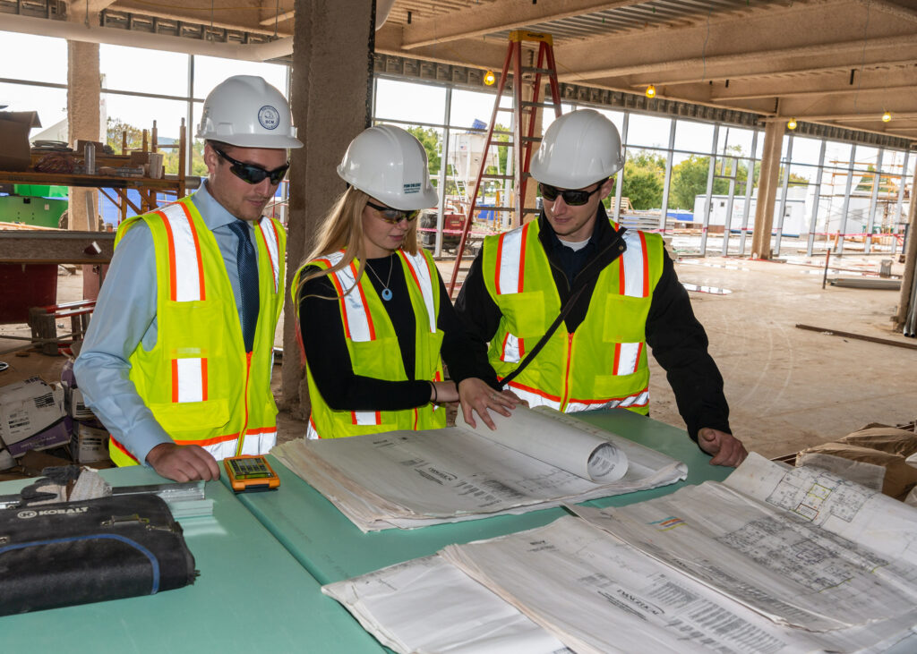 A group of students with blueprints on a job site.