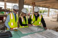 A group of students gathered around blueprints on a jobsite.